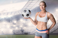 Composite image of female athlete holding a soccer ball. Female athlete holding a soccer ball against sports arena royalty free stock photos