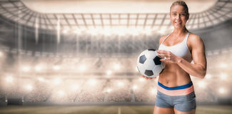 Composite image of female athlete holding a soccer ball. Female athlete holding a soccer ball against sports arena royalty free stock photography