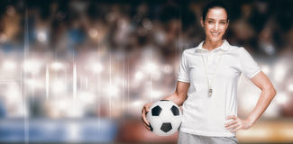 Composite image of female athlete holding a soccer ball. Female athlete holding a soccer ball against sports arena stock photos