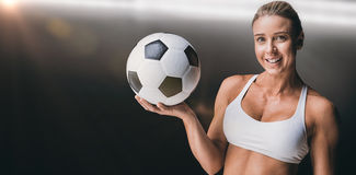 Composite image of female athlete holding a soccer ball. Female athlete holding a soccer ball against spotlight stock photo