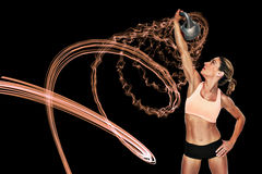 Composite image of female blonde crossfitter lifting kettlebell above head Royalty Free Stock Image