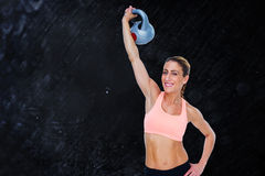 Composite image of female blonde crossfitter lifting kettlebell above head smiling at camera Royalty Free Stock Photo