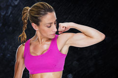 Composite image of female bodybuilder flexing bicep in pink sports bra Stock Image