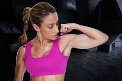 Composite image of female bodybuilder flexing bicep in pink sports bra Stock Photo