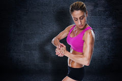 Composite image of female bodybuilder flexing in pink sports bra Royalty Free Stock Photos