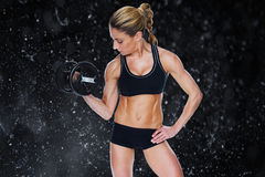 Composite image of female bodybuilder holding large black dumbbell with arm up looking at bicep. Female bodybuilder holding large black dumbbell with arm up Royalty Free Stock Image