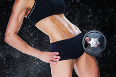 Composite image of female bodybuilder holding large black dumbbell mid section Royalty Free Stock Photo