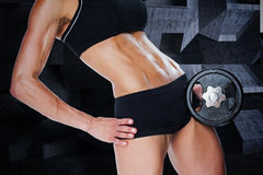 Composite image of female bodybuilder holding large black dumbbell mid section Stock Image