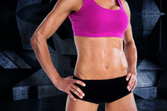 Composite image of female bodybuilder posing with hands on hips mid section Royalty Free Stock Image