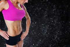 Composite image of female bodybuilder posing in pink sports bra Stock Photography
