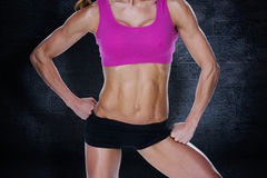 Composite image of female bodybuilder posing in pink sports bra and shorts mid section Royalty Free Stock Images