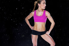 Composite image of female bodybuilder posing in sports bra and shorts. Female bodybuilder posing in sports bra and shorts against black background stock illustration