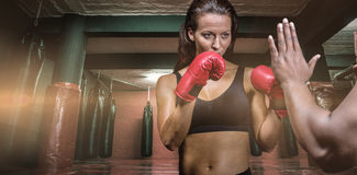 Composite image of female boxer with fighting stance against trainer hand Royalty Free Stock Image