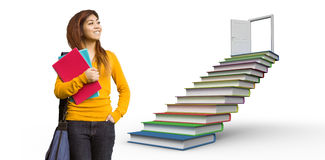 Composite image of female college student with books in park. Female college student with books in park against steps made from books leading to open door stock photo
