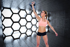 Composite image of female crossfitter lifting up kettlebell Royalty Free Stock Image