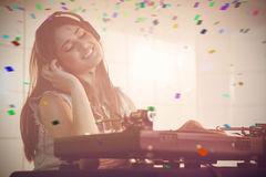 Composite image of female dj listening to headphone while playing music Royalty Free Stock Photography