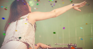 Composite image of female dj playing music while waving hand. Female DJ playing music while waving hand against flying colours Royalty Free Stock Image