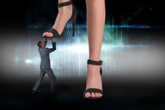 Composite image of female feet in black sandals stepping on businessman Royalty Free Stock Photos