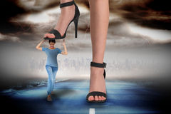 Composite image of female feet in black sandals stepping on girl Stock Photo