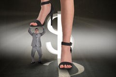 Composite image of female feet in black sandals stepping on tiny businessman Royalty Free Stock Image
