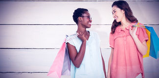 Composite image of female friends holding shopping bags Royalty Free Stock Photo