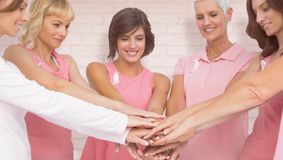 Composite image of female friends stacking hands for breast cancer awareness Stock Image