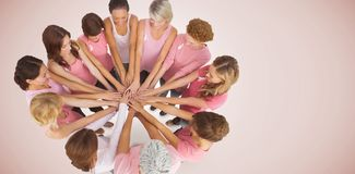 Composite image of female friends supporting breast cancer. Female friends supporting breast cancer against neutral background Stock Images