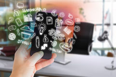 Composite image of female hand holding a smartphone 3d. Female hand holding a smartphone against blurry picture of computer on desk 3d Royalty Free Stock Photography