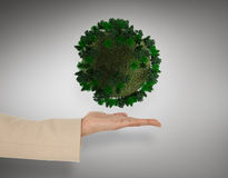 Composite image of female hand presenting green sphere. Female hand presenting green sphere against grey vignette Royalty Free Stock Photo