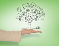 Composite image of female hand presenting light bulb tree Royalty Free Stock Photos
