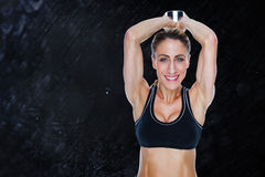 Composite image of female happy bodybuilder working out with large dumbbell behind head Stock Image