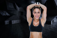 Composite image of female happy bodybuilder working out with large dumbbell behind head Royalty Free Stock Photos