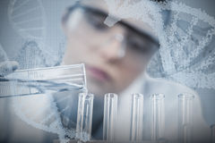 Composite image of female scientist pouring chemical Royalty Free Stock Photo