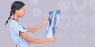 Composite image of female surgeon examining chest x-ray. Female surgeon examining chest X-ray against salmon background royalty free stock images