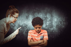Composite image of female teacher shouting at boy. Female teacher shouting at boy against dark background Stock Photography