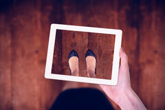 Composite image of feminine hand holding tablet Royalty Free Stock Image