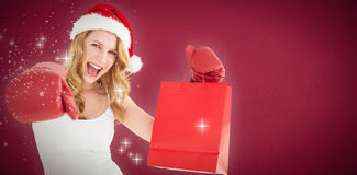 Composite image of festive blonde with boxing gloves and shopping bag Stock Photos