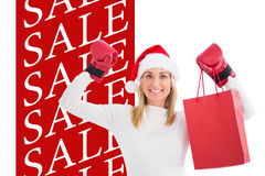Composite image of festive blonde in boxing gloves with shopping bag Stock Photography
