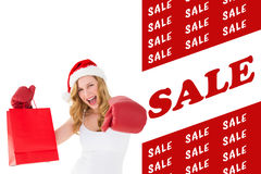 Composite image of festive blonde with boxing gloves and shopping bag Royalty Free Stock Photography