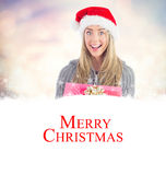 Composite image of festive blonde holding christmas gift. Festive blonde holding christmas gift against glowing christmas background Stock Photos