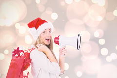Composite image of festive blonde holding megaphone and bags Stock Images