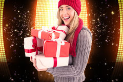 Composite image of festive blonde holding pile of gifts Royalty Free Stock Photos