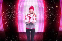 Composite image of festive blonde holding pile of gifts Royalty Free Stock Image
