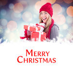 Composite image of festive blonde holding pile of gifts Stock Photography