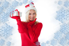 Composite image of festive blonde holding a present Stock Photos