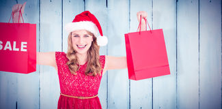 Composite image of festive blonde holding sale shopping bags Royalty Free Stock Photography