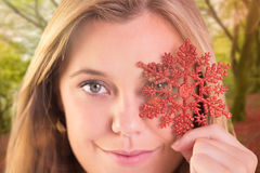 Composite image of festive blonde holding a snowflake Royalty Free Stock Photography