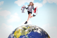 Composite image of festive blonde jumping with shopping bags Stock Photo