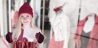 Composite image of festive blonde opening a gift bag Stock Image