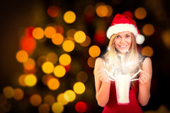 Composite image of festive blonde opening a gift bag Royalty Free Stock Photos